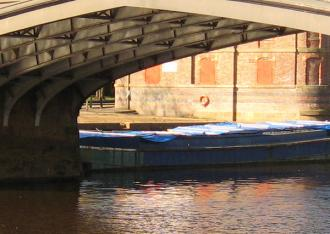 View of barge on river, under bridge