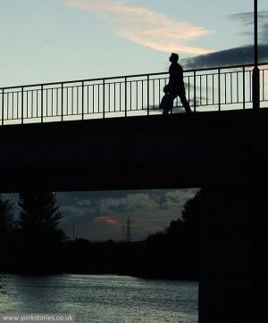 Silhouette of pedestrian on bridge at sunset
