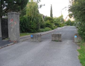 View of road with concrete blocks across and pillar to one side