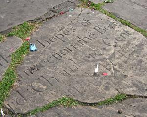 Old headstone, littered with pieces of disposable plastic fork