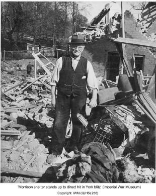 Man standing in ruins of bombed house