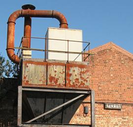 Rusty iron structure and 'SAWMILL' sign