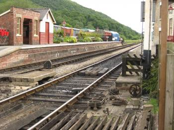 Railway lines in foreground, station platforms and hillside behind