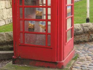 Advertising fliers in panes of traditional red phone box
