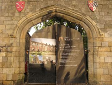 Stone wall, arched gateway, city arms above, developer's advertising on gates, reflecting fuzzy images
