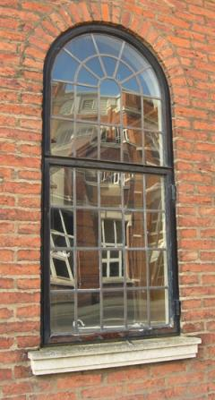 Leaded windows, panes reflecting distorted view of building opposite
