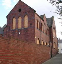 Boarded-up Victorian school building, over brick wall of adjoining alleyway