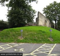 View of mound and city walls rampart, looking up, across car park area