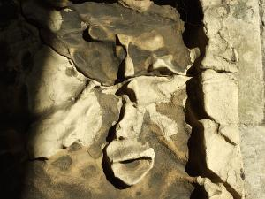 Stone in wall, worn away to leave a shape suggesting part of a face, with puckered lips, as if to kiss