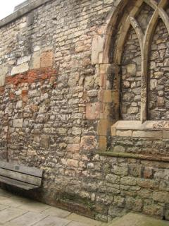Blocked-up church window, brick and stone wall, empty bench
