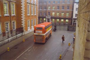 A cheery red bus on a gloomy wet day