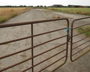 Concrete runway, through iron gate, with crops surrounding it