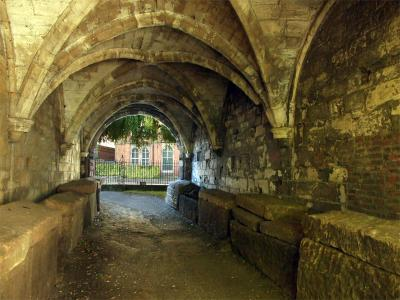 Tunnel from end to end, in perspective, walls lined with stone coffins, with lids
