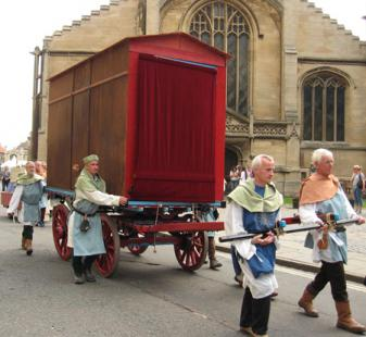 Men pulling and pushing pageant waggon past church