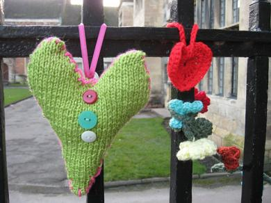 Knitted hearts hanging from black-painted railings