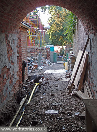 Brick tunnel/archway, with building site beyond