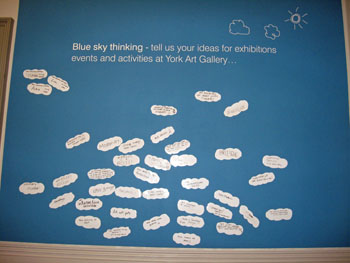 Handwritten ideas on cloud-shaped labels stuck to a display board