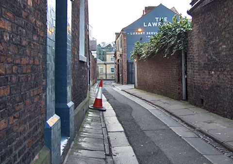 Narrow lane with red brick walls and painted ad on gable end
