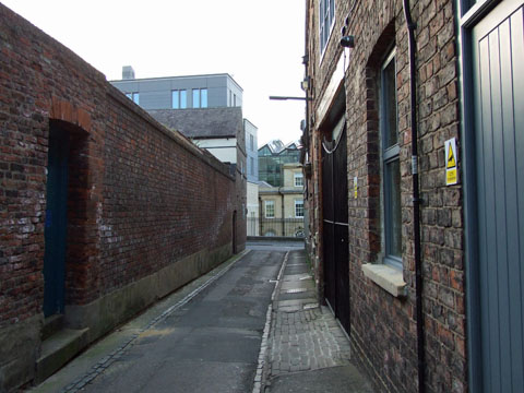 Old red brick buildings and garden wall on narrow ancient lane