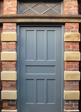 Large grey-painted door with brick and stone surround