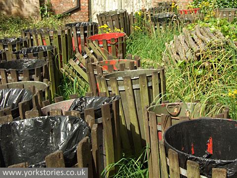 Many abandoned bins, among weeds