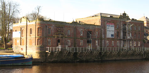 Large Victorian riverside warehouse, with river in front, and For Sale sign attached