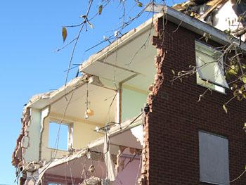 Part-demolished building, ragged brick edge, painted interior walls visible