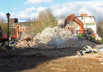 View of machinery, rubble, workers on demolition site