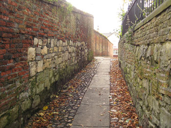 Alley between brick and stone walls, crooked, ancient, cobbled
