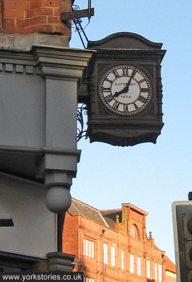 Clock on projecting bracket, showing maker's name