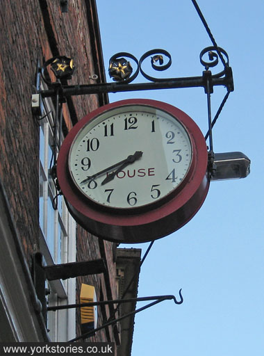 Clock face says HOUSE (former occupier, House and Son electricals)