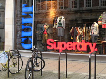 Front of Cult store, with Superdry branding. Bikes parked in racks outside.
