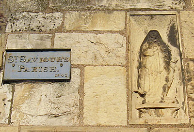 Sign for 'St Saviour's Parish' on stone wall with embedded figure/effigy
