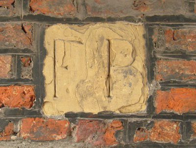 Brick wall with inset stone carved with 'FP'