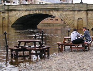 Drinkers at outdoor tables, river floodwater approaches