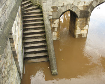 Flood waters lapping at bottom of stone steps and city wall