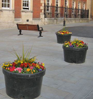 Spring flowers in black plastic tubs on stone paving