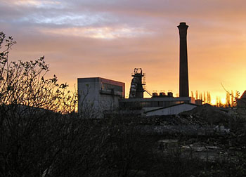 Sunset over an industrial scene, with chimney in silhouette