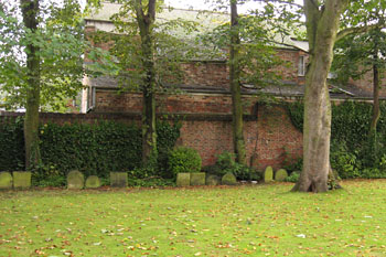 Lawned area, gravestones in front of high walls, old red brick