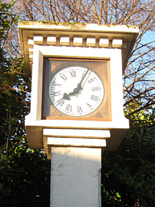 Outdoor clock in front of trees, by factory entrance, time: 8:05