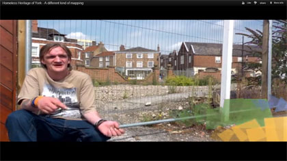 Man sitting by wire fencing around demolition site