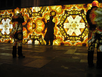Light projections on cathedral stone wall giving stained glass effect