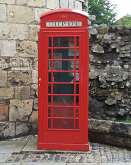 Red phone box against stone walls