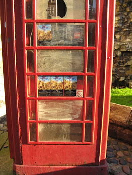 Phone box looking scruffy, with graffiti and fliers