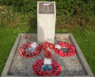 Stone memorial, with metal plaque, poppy wreaths beneath