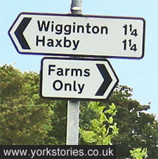 Sign shows distance to nearby places, and also 'Farms only'