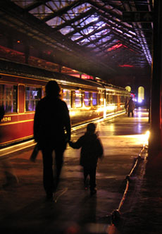 Figures in silhouette against lit-up train in dark hall