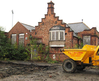 Victorian school building, muddy ground and digger