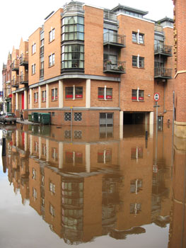 Flood water reflecting buildings in street