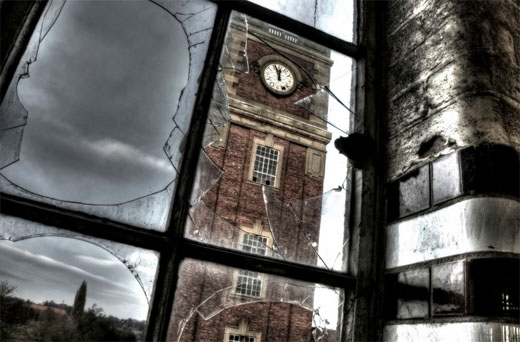 Brick clock tower with clock, viewed through broken glass of factory window